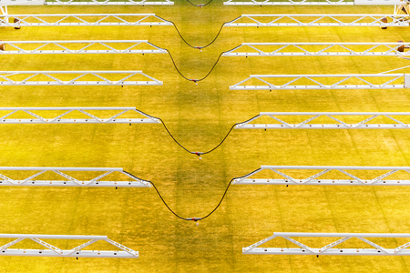 Cables between artificial light lamps for growing lawns at football stadiums.