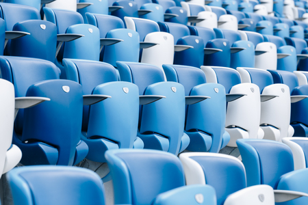 Multi-colored armchairs with numbers on a football stadium. Blue and white color Reklamní fotografie - 106224133