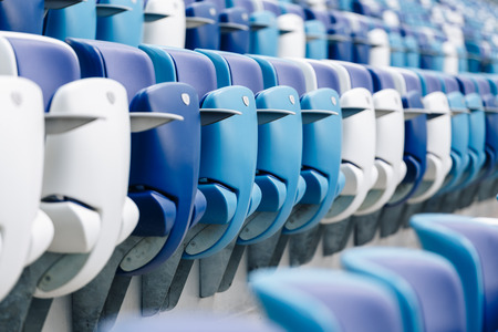 Multi-colored armchairs with numbers on a football stadium. Blue and white color Reklamní fotografie - 106224138