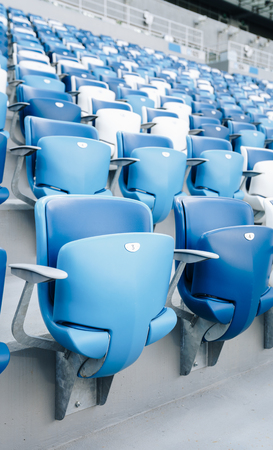 Multi-colored armchairs with numbers on a football stadium. Blue and white color Reklamní fotografie - 106224139