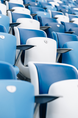 Multi-colored armchairs with numbers on a football stadium. Blue and white color Reklamní fotografie - 106224142