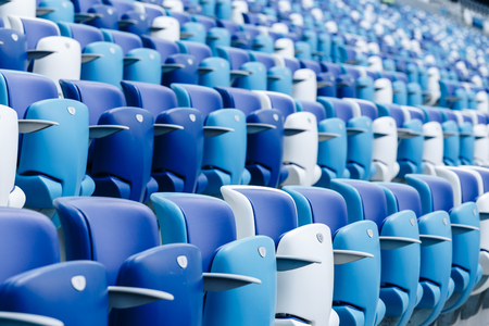 Multi-colored armchairs with numbers on a football stadium. Blue and white color Reklamní fotografie - 106224140