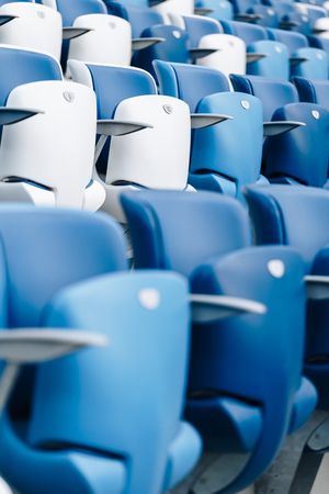 Multi-colored armchairs with numbers on a football stadium. Blue and white color Reklamní fotografie - 106224144
