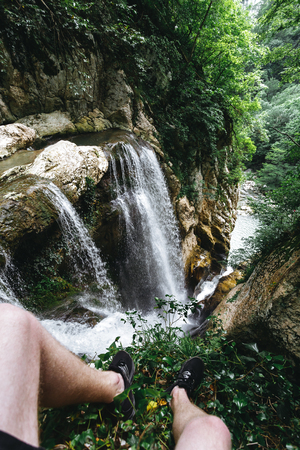 A guy in black shorts and sneakers sits on the edge of a rock in front of a large waterfall in the Agur gorge Reklamní fotografie - 106222317