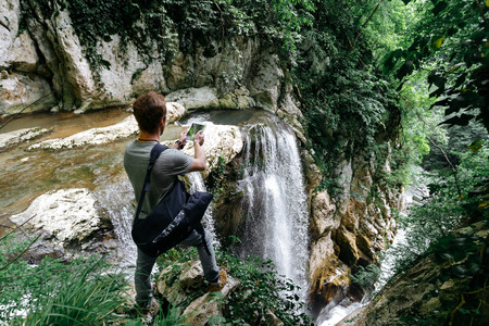 A traveler with a phone takes a picture of a large waterfall in the Agur gorge on the edge of a cliff.