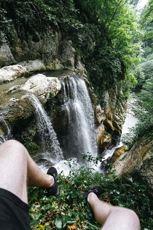 A guy in black shorts and sneakers sits on the edge of a rock in front of a large waterfall in the Agur gorge