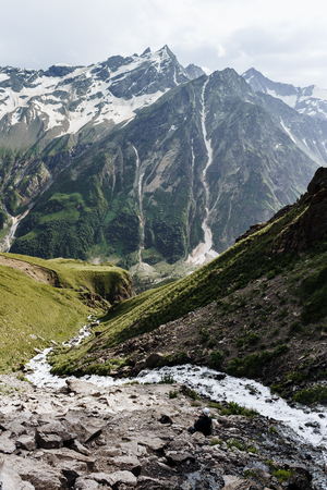 The mountain river flows between the rocks in the mountains of the Elbrus region.