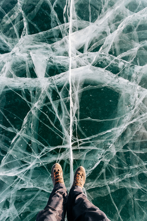 Feet in the boot stand on the green ice with huge cracks Reklamní fotografie - 126270080