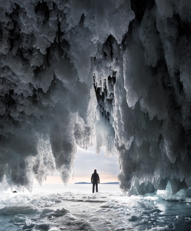 Silhouette of a man in a cave covered with blue ice and icicles Banco de Imagens