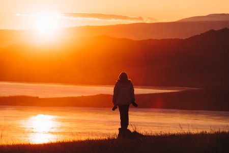 Girl watching sunset on a stone against the background of mountains and the sea. Reklamní fotografie - 126270434