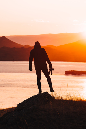 Male traveler stands alone at sunset against the background of water and mountains Reklamní fotografie - 126270448