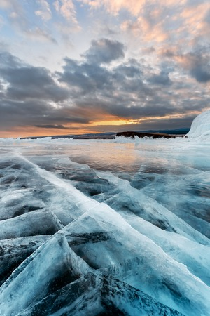 Huge cracks in the ice of the lake on the background of a beautiful sunset. Baikal, Russia.
