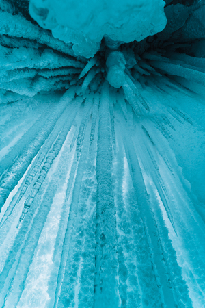 Turquoise and blue icicles. Ice hangs in an ice cave. Baikal, Russia.