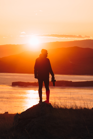 Male traveler stands alone at sunset against the background of water and mountains