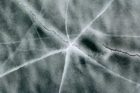 Texture and pattern of cracks in frozen ice.