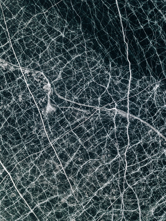 Texture and pattern of cracks in frozen ice. Reklamní fotografie - 126270532