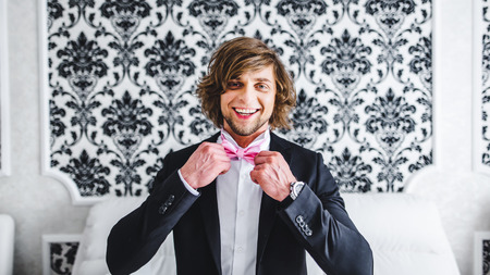 butterfly bow: Man the groom in a wedding formal costume with butterfly. Suit, Hands, care, tie, to correct, to adjust, fashion, bow. Instagram colors toning Stock Photo