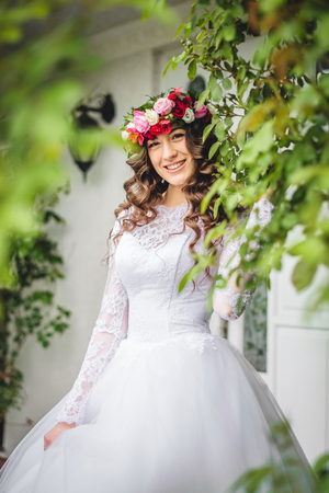Bride with wreath standing outside in front of a door Stock Photo