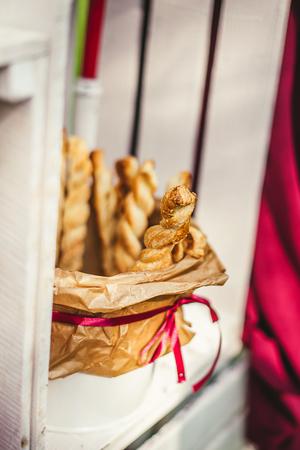 Tasty breadsticks in paper basket. Food on wooden background
