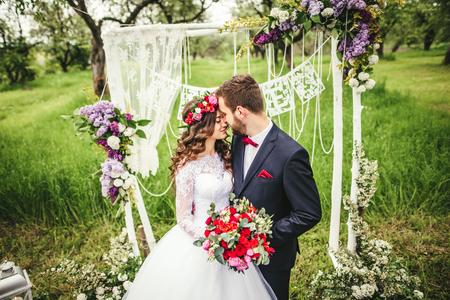 bride and groom outdoors. wedding ceremony. wedding arch.