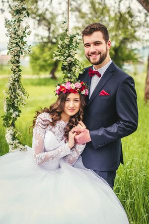 Schöne wunderschöne Brünette Braut und stilvolle Bräutigam auf dem geschmückten Schaukel auf dem Baum Standard-Bild - 64056754
