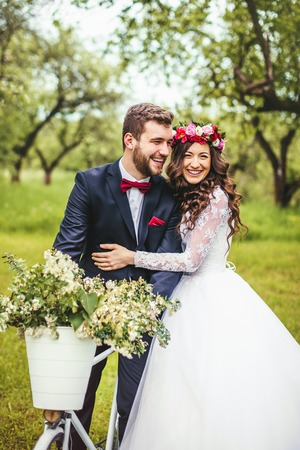 Beautiful bride & groom posing near vintage provence bicycle outdoor