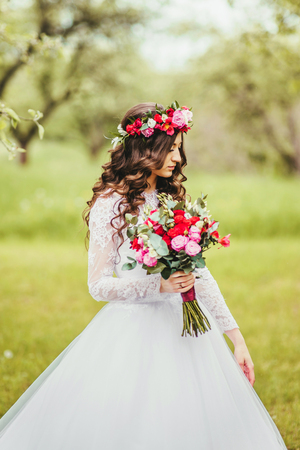 Wedding. Young beautiful bride in white dress and wreath standing at green lawn between trees. Summer full length atmospheric portrait portrait.