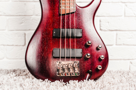 Rosewood bass electric guitar with four strings near the white brick wall closeup