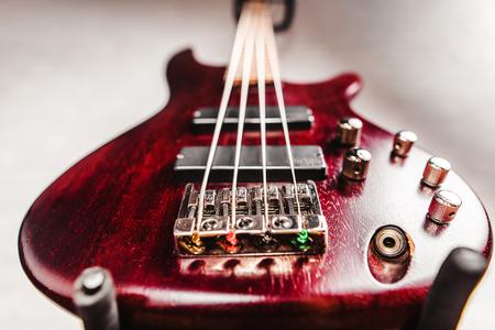 Rosewood bas elektrische gitaar met vier snaren in de buurt van de witte bakstenen muur close-up Stockfoto