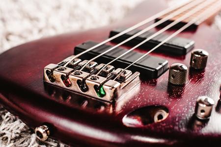 회색 카펫 근접 촬영에 4 개의 문자열과 로즈 우드베이스 일렉트릭 기타