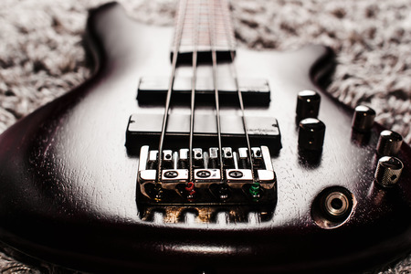 Rosewood bass electric guitar with four strings on the gray carpet closeup Stock Photo
