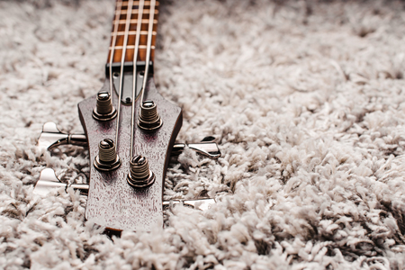 close up of the head of an electric four sting bass on the carpet