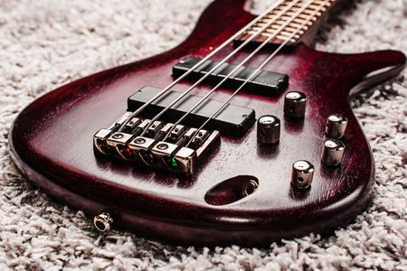 Rosewood bas elektrische gitaar met vier snaren op de grijze tapijt close-up
