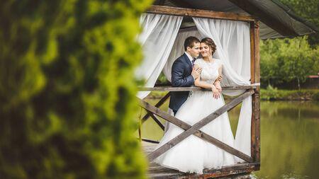 Wedding couple, bride, groom posing on pier Stock Photo