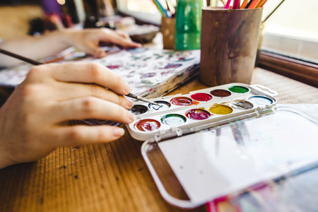 Girls hands with brush painting with watercolor paints Stock Photo