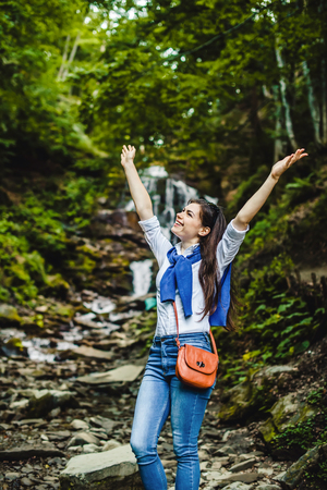 Happy young woman spreading hands enjoying nature with waterfall in background.