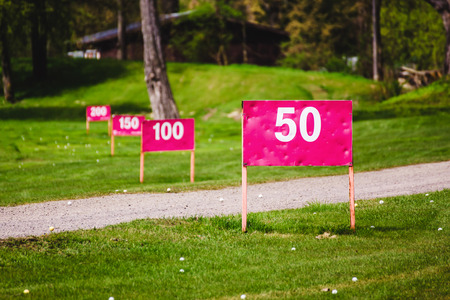 Yard signs in driving range and golf ball? in golf course