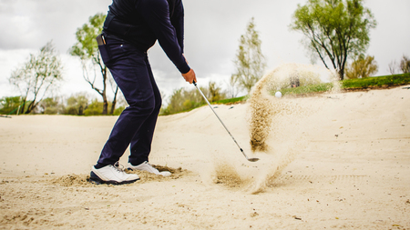 Golfplayer schlägt einen ball in den sand Standard-Bild - 80695989