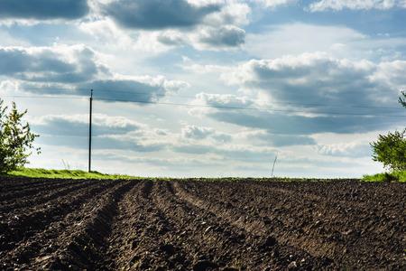 검은 토양은 들판과 푸른 구름을 쟁기로 만들었다. 스톡 콘텐츠