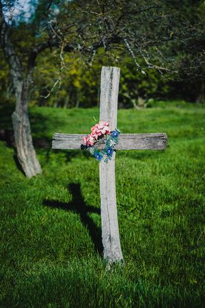 Hölzernes Kreuz mit Blumen im Garten Standard-Bild - 81457481