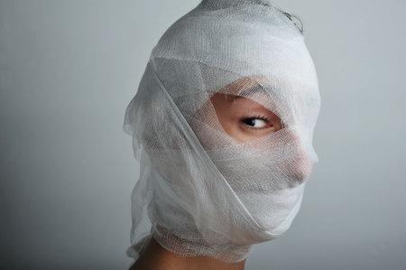 bandaged: Young man portrait with bandaged face, close up