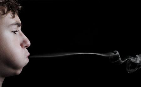 Portrait d'un gar�on de fumer sur fond noir