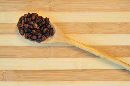 Close up of a wooden spoon with coffee beans  photo