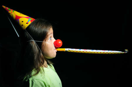 blowers: Portrait of a girl with party horn blowing in blowers Stock Photo