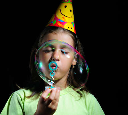 childrens birthday party: Little girl blowing soap bubbles, childrens birthday party