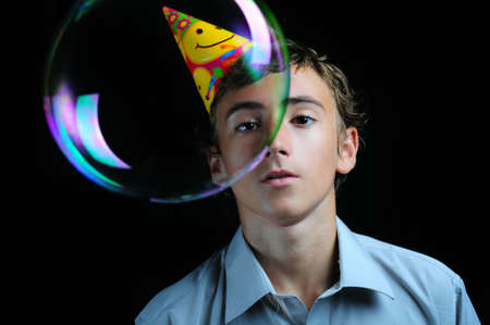 childrens birthday party: Young boy looking through soap bubbles, childrens birthday party