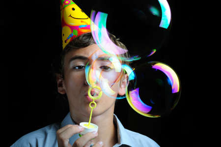 childrens birthday party: Young boy blowing soap bubbles, childrens birthday party