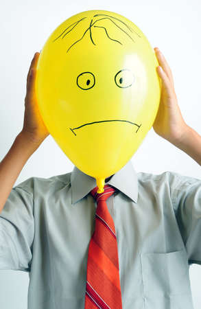 woeful: Young boy holding a yellow balloon in front of his face Stock Photo