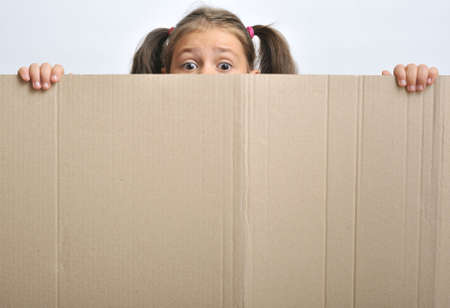 adequate: Little girl behind a blank cadboard (adequate for text), close up
