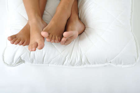 white pillow: Foot resting on a white pillow, close up